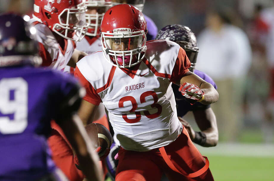 Raiders running back Christian Mallard squares off with a defensive back after getting past the line in the first half as Taft plays Warren at Gustafson Stadium on Oct. 29, 2015. Photo: Tom Reel /San Antonio Express-News