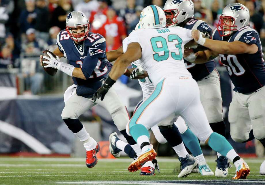 Patriots QB Tom Brady, left, proved too much to handle for Ndamukong Suh and the Dolphins. Photo: Michael Dwyer, STF / AP