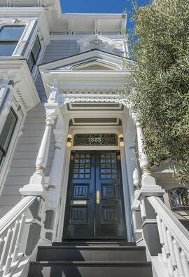 A  portico supported by a quartet of pillars leads to dual entry doors and the home's stately foyer.