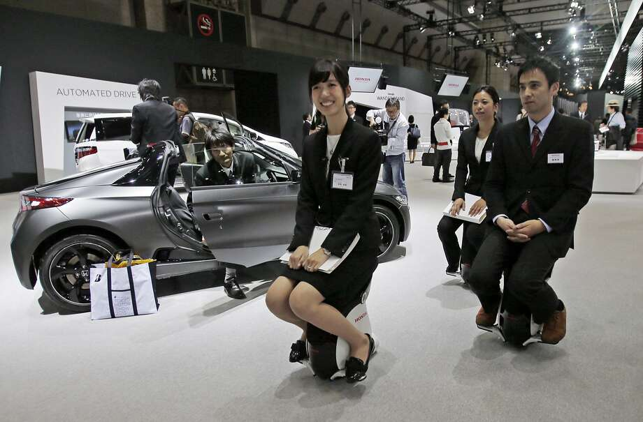 Honda Motor Co. employees ride on Honda UNI-CUB fl through the Japanese automaker's booth during the media preview of the Tokyo Motor Show in Tokyo Wednesday, Oct. 28, 2015. The biennial exhibition of vehicles in Japan runs for the public from Friday, Oct. 30. Photo: Shuji Kajiyama, Associated Press