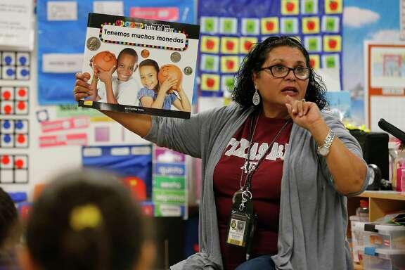 Teacher Mary Helen Romero's conducts a lesson to her first-grade class in Spanish. The children learn in a dual language environment where a major portion of their lessons are taught in Spanish and the rest in English at Adams Elementary on Wednesday, Oct. 28, 2015. This approach has garnered Harland Independent School District recognition for their dual language strategies by the New American Foundation. Both English and Spanish-dominant language students are enrolled in Mrs. Romero's class. (Kin Man Hui/San Antonio Express-News)