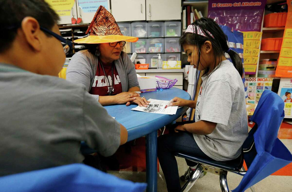 First-grade student Cristina Morales (right) reads in Spanish to teacher Mary Helen Romero (center) during dual language class at Adams Elementary on Wednesday, Oct. 28, 2015. Students are being taught in a dual language environment where a major portion of their lesson are in Spanish and the rest in English. This approach has garnered Harland Independent School District recognition for their dual language strategies by the New American Foundation. Both English and Spanish-dominant language students are enrolled in Mrs. Romero's class. (Kin Man Hui/San Antonio Express-News)