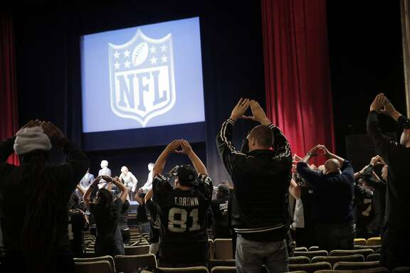 """Oakland Raiders fans recite """"The Autumn Wind"""" as members of NFL Commissioner Roger Goodell's staff held a public hearing on the idea of the Raiders football team moving to southern California at the Paramount Theater in Oakland, Calif., on Thursday, October 29, 2015."""