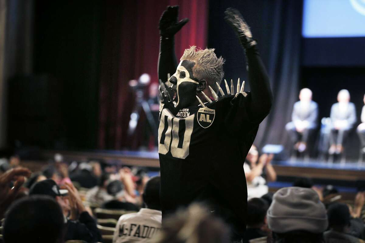 Oakland Raiders fan Joey Seimas from Fresno cheers on other fans after making his comments as members of NFL Commissioner Roger Goodell's staff held a public hearing on the idea of the Raiders football team moving to southern California at the Paramount Theater in Oakland, Calif., on Thursday, October 29, 2015.