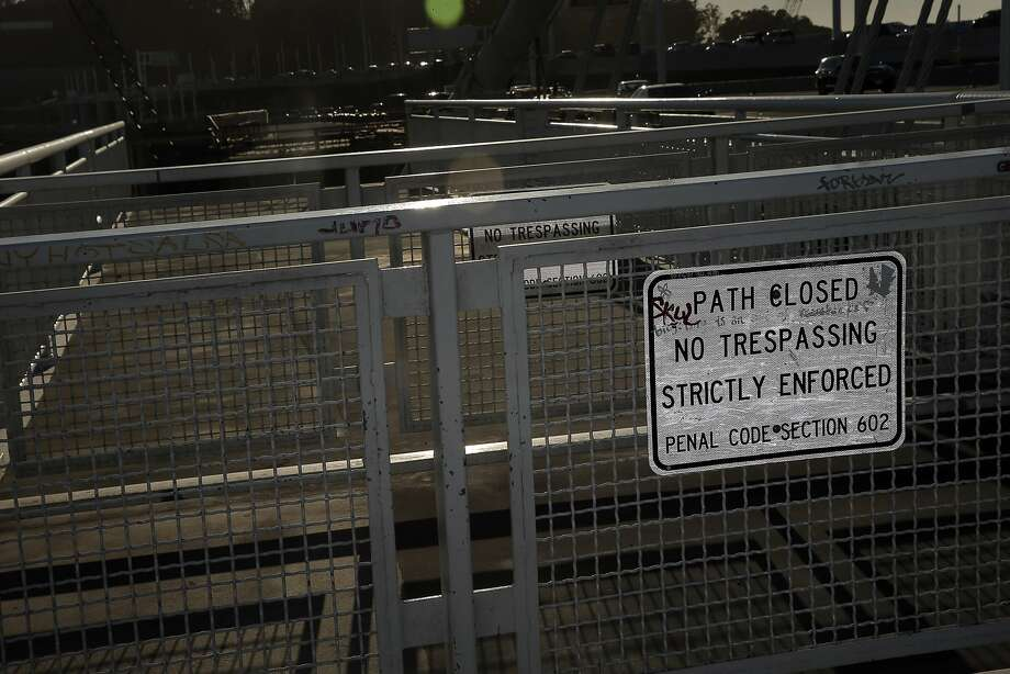 Signs and a gate greet pedestrians and bicyclists at the end of the Pedestrian and Bicycle Path on the Bay Bridge in Oakland, Calif., on Thursday, October 29, 2015. The Bay Bridge bike path from Oakland to Treasure Island has been delayed yet again. Originally scheduled to open along with the new eastern span two years ago, completion had to wait for demolition of part of the old span, which was to be completed by summer. Then it was delayed until late fall/end of the year. Now, it looks like bike riders won't be able to pedal from the East Bay to Treasure Island until sometime next year. Photo: Carlos Avila Gonzalez, The Chronicle