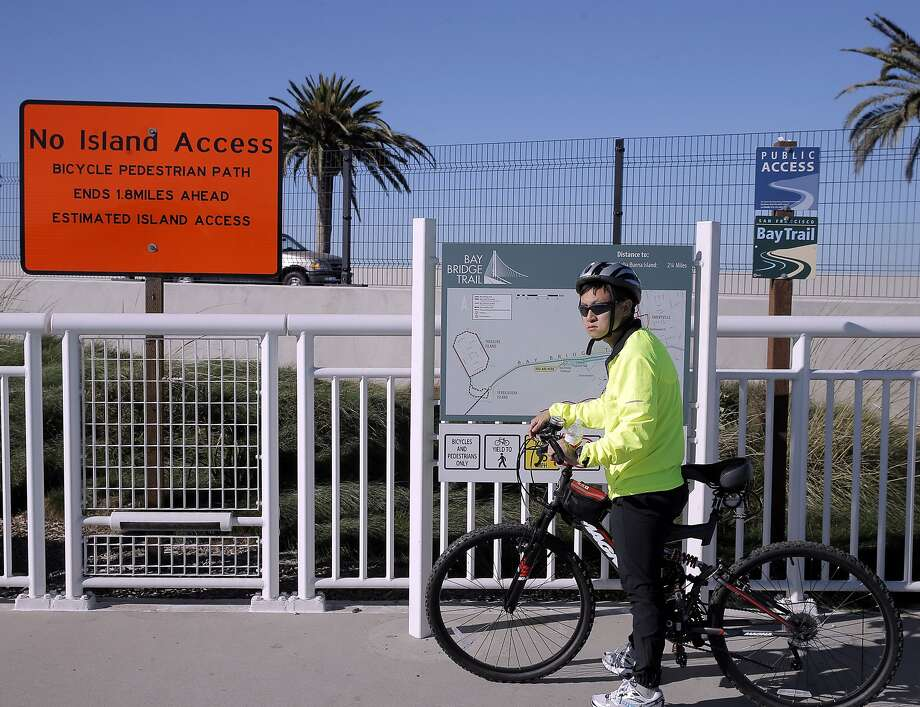 Eugene Lai stands near a Caltrans sign showing there is no access to Treasure Island on the Bicycle Pedestrian Path in Oakland, Calif., on Thursday, October 29, 2015. The Bay Bridge bike path from Oakland to Treasure Island has been delayed yet again. Originally scheduled to open along with the new eastern span two years ago, completion had to wait for demolition of part of the old span, which was to be completed by summer. Then it was delayed until late fall/end of the year. Now, it looks like bike riders won't be able to pedal from the East Bay to Treasure Island until sometime next year. Photo: Carlos Avila Gonzalez, The Chronicle