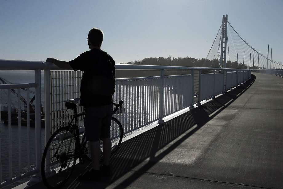 Andy Roth of Berkeley, looks out over the demolition of the old Bay Bridge from the Bicycle Pedestrian Path in Oakland, Calif., on Thursday, October 29, 2015. The Bay Bridge bike path from Oakland to Treasure Island has been delayed yet again. Originally scheduled to open along with the new eastern span two years ago, completion had to wait for demolition of part of the old span, which was to be completed by summer. Then it was delayed until late fall/end of the year. Now, it looks like bike riders won't be able to pedal from the East Bay to Treasure Island until sometime next year. Photo: Carlos Avila Gonzalez, The Chronicle