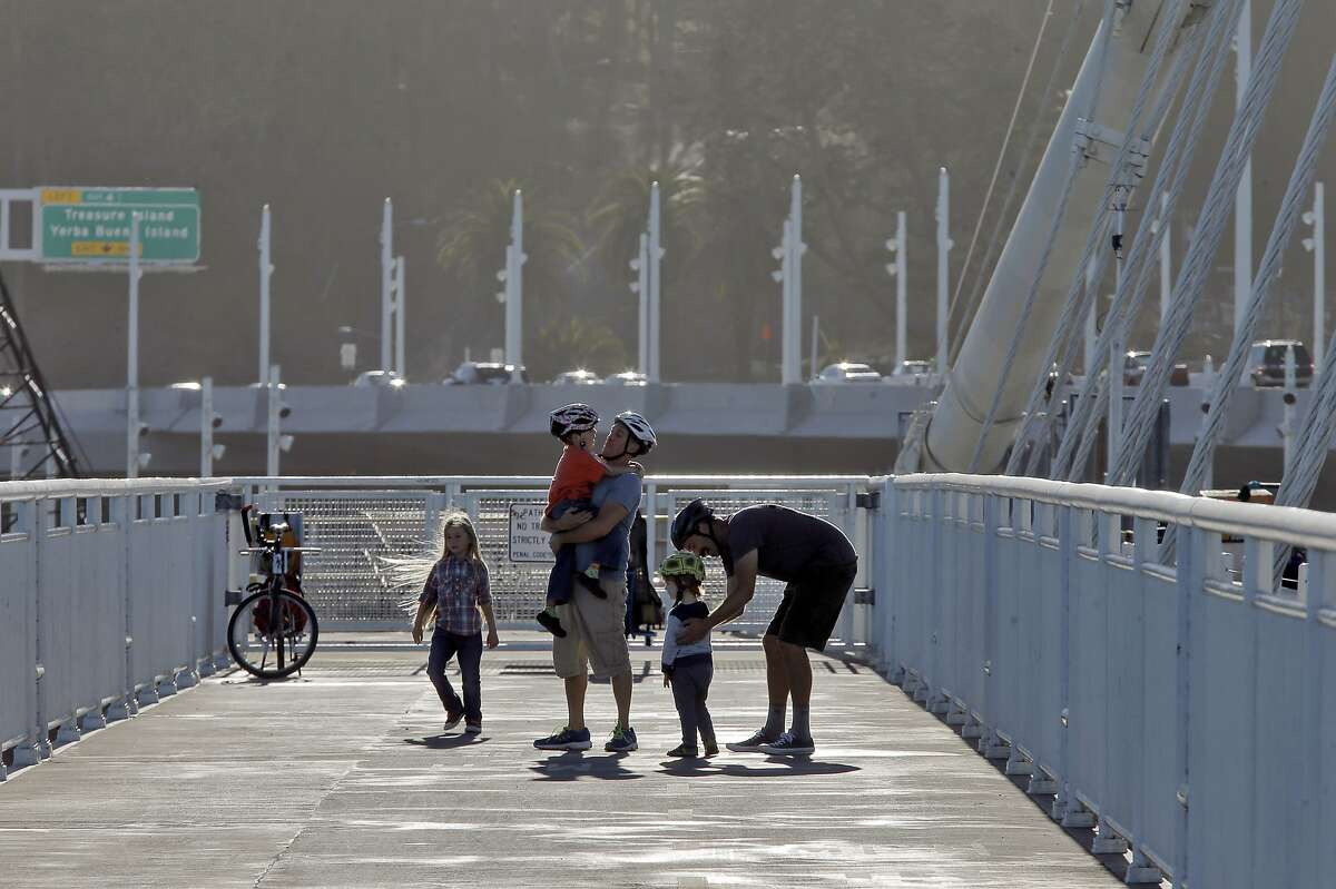 Joel Tornatore, center, holds his son Jeffery, 5, as Joel DeVries, right, checks on his son Ellis, 2, and his other son Noah, 5, walks nearby on the left of the Bicycle Pedestrian Path on the Bay Bridge in Oakland, Calif., on Thursday, October 29, 2015. The Bay Bridge bike path from Oakland to Treasure Island has been delayed yet again.