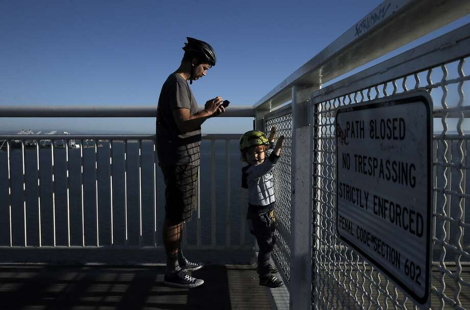 Joel DeVries, left, and his son Ellis, 2, look out over the fence at the end of the Bicycle Pedestrian Path on the Bay Bridge in Oakland, Calif., on Thursday, October 29, 2015. The Bay Bridge bike path from Oakland to Treasure Island has been delayed yet again. Originally scheduled to open along with the new eastern span two years ago, completion had to wait for demolition of part of the old span, which was to be completed by summer. Then it was delayed until late fall/end of the year. Now, it looks like bike riders won't be able to pedal from the East Bay to Treasure Island until sometime next year. Photo: Carlos Avila Gonzalez, The Chronicle