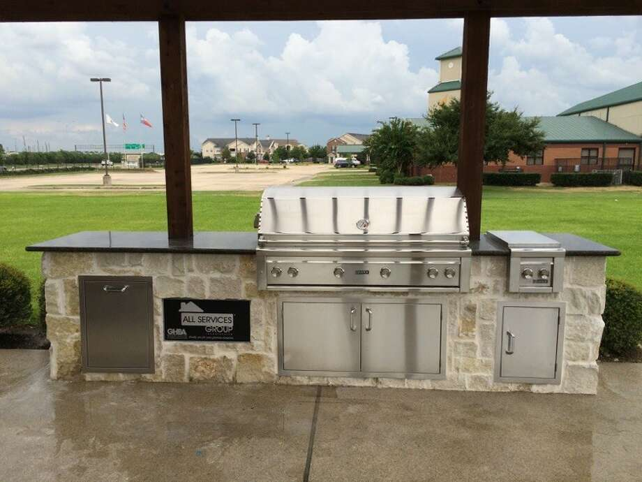 This is an outdoor kitchen that features granite and appliances. Photo: All Service Group