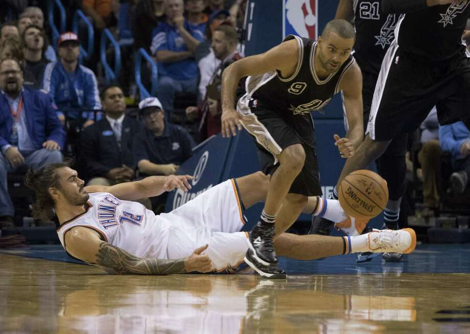 Tony Parker of the Spurs steals the ball as Steven Adams of the Oklahoma City Thunder falls to the floor during the fourth quarter on Oct. 28, 2015 in Oklahoma City. Photo: J Pat Carter /Getty Images / 2015 Getty