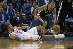 Tony Parker of the Spurs steals the ball as Steven Adams of the Oklahoma City Thunder falls to the floor during the fourth quarter on Oct. 28, 2015 in Oklahoma City.