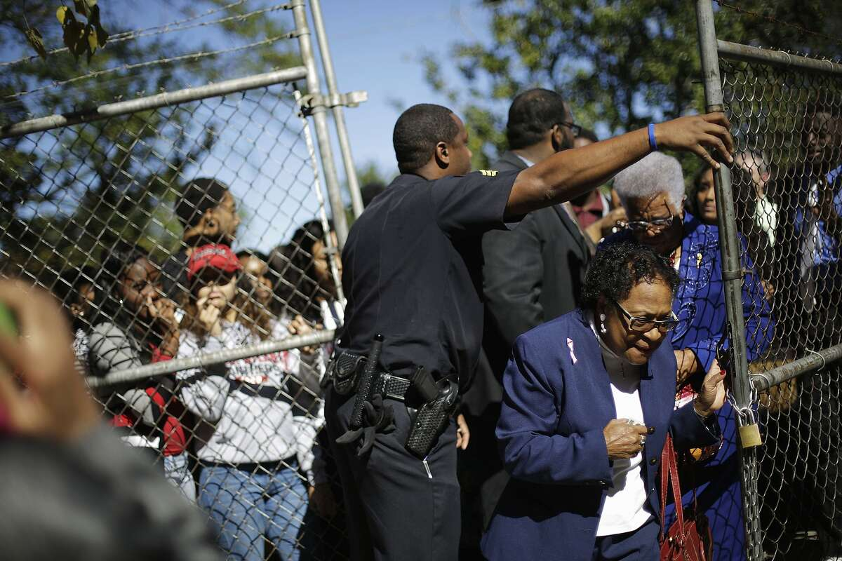 A police officer lets in some members of the public in as they line up to see Democratic presidential candidate Hillary Rodham Clinton speak at a campaign event at Clark Atlanta University in Atlanta, Friday, Oct. 30, 2015. (AP Photo/David Goldman)