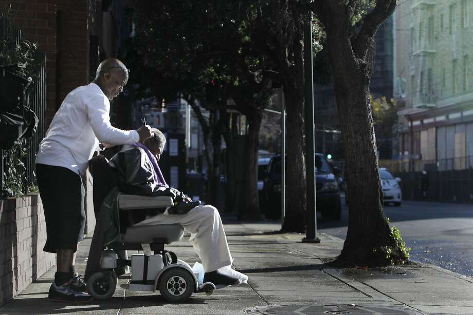 Lloyd Lopez of San Francisco cuts his uncle Mac Blake's hair in the morning sun on the sidewalk across the street from the Renoir Hotel on Thursday, October 29,  2015 in San Francisco, Calif. Photo: Lea Suzuki, The Chronicle