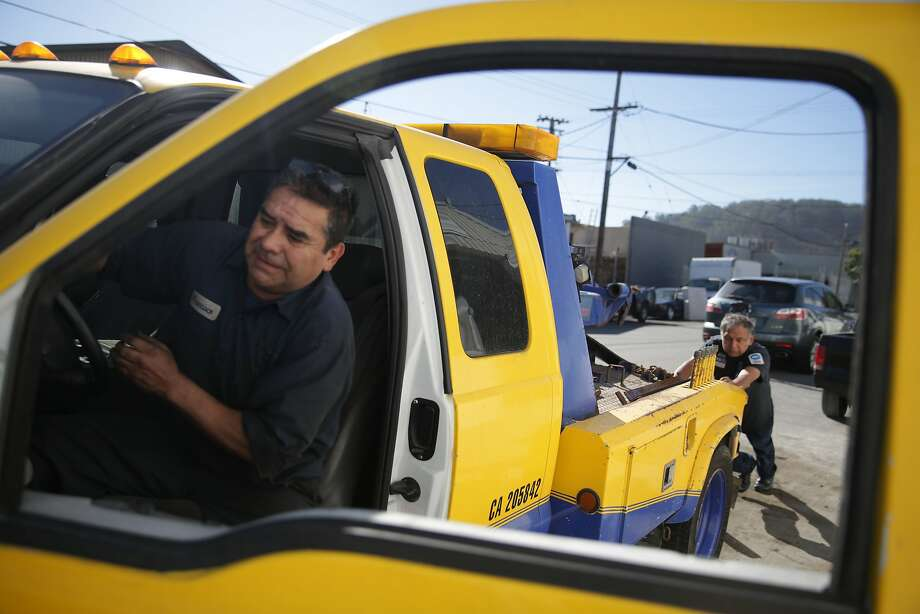 Francisco Martinez (l to r) and  Jose de Jesus, both with GR Automotive, work together to move a stalled truck into a parking space on Friday, October 30,  2015 in San Francisco, Calif. Photo: Lea Suzuki, The Chronicle