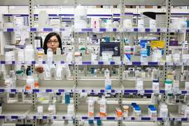 Lisa Fung, pharmacist at Walgreens Pharmacy, looks for the correct medicine to fill a prescription at Walgreens Pharmacy, in San Francisco, California on Friday, October 30, 2015.