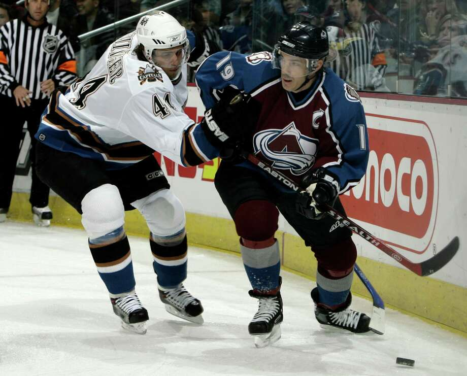 Washington Capitals defenseman Steve Eminger, left, keeps Colorado Avalanche center Joe Sakic in check as he tries to work the puck in for a shot in the first period of an NHL hockey game in Denver on Oct. 25, 2006. Photo: Associated Press File Photo / AP