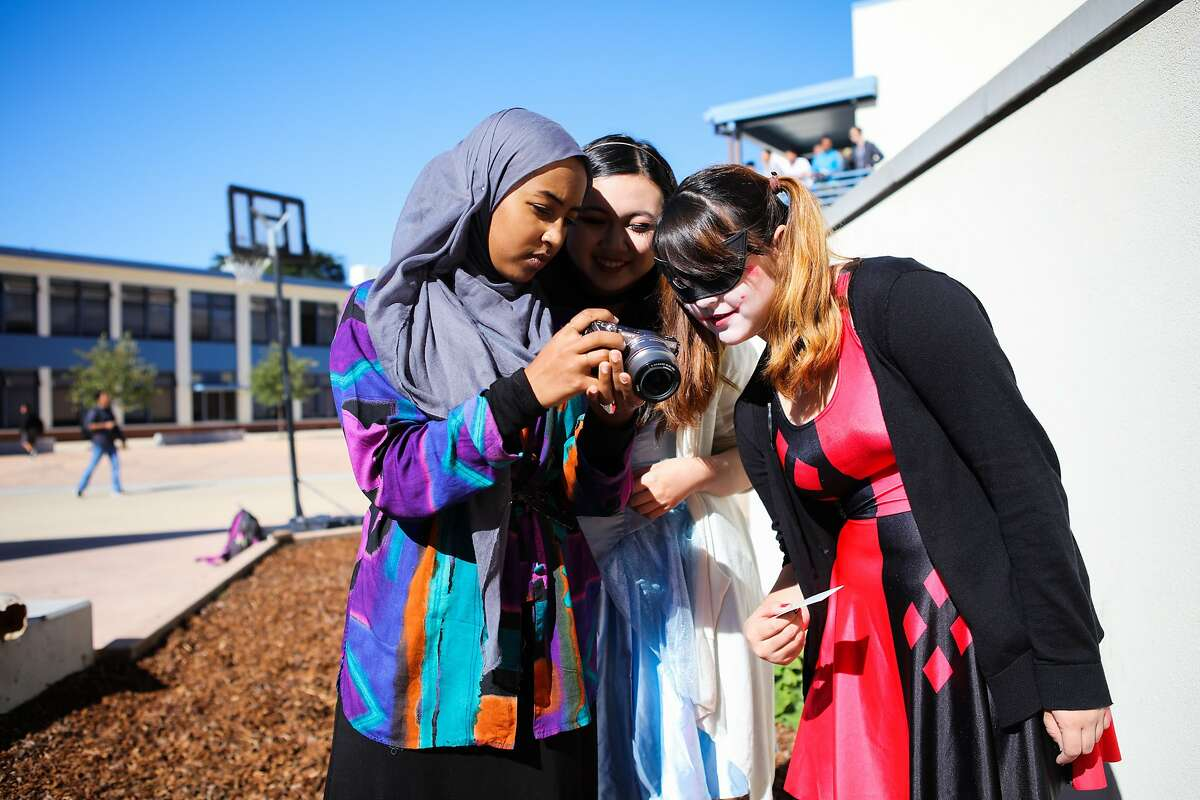 Mai Sinada (left), Erica Lee (center) and another friend look at a photo that Mai has taken of them in their Halloween costumes at Wallenberg High School in San Francisco, California on Friday, October 30, 2015.
