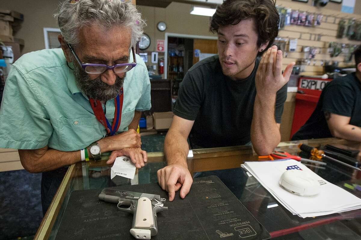 Sales associate Chris Harris, right, talks to Elliott Isenberg about his Colt .45 handgun at High Bridge Arms, Friday, Oct. 30, 2015, in San Francisco, Calif. Isenberg bought the last gun sold at the store.