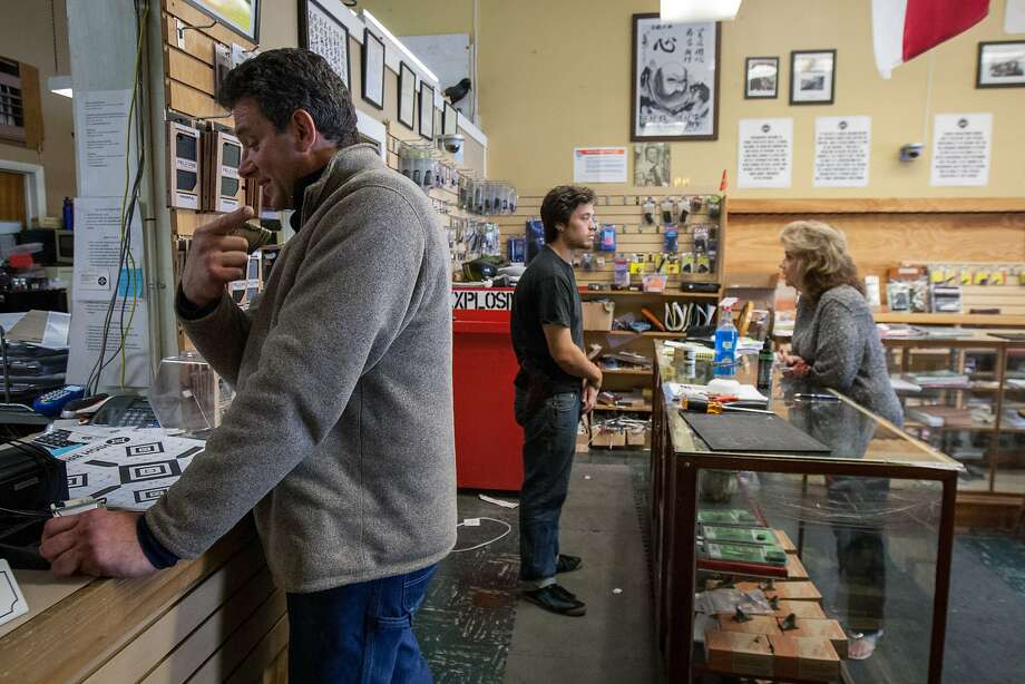 Dino DeSantis (left) buys practice targets as a souvenir from High Bridge Arms on Oct. 30. High Bridge Arms, the city's last gun shop, is closing because  of a new city ordinance that requires gun sellers to video-record all commercial firearms sales, as well as give the Police Department weekly updates on ammunition sales. Photo: Santiago Mejia, Special To The Chronicle