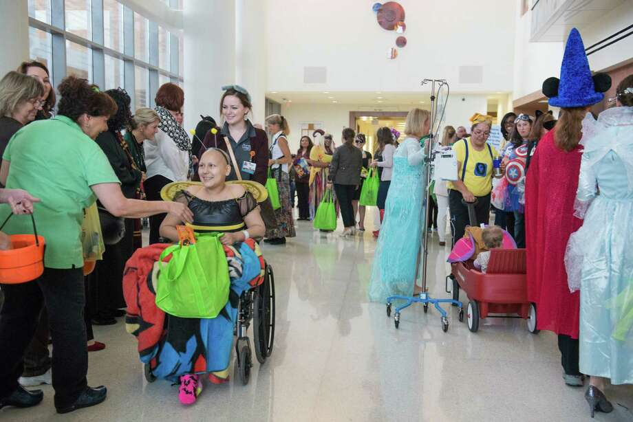 Jurnee Cano, 18, who suffers from sarcoma, left, was in the hospital today for her regular clinic visit when she was handed a bee costume and told she could participate in University Hospital's annual Pediatric Parade in San Antonio on Friday, October 30, 2015. University Hospital's annual Pediatric Parade includes current and former pediatric patients dressed in costumes and trick-or-treating through the hospital's Sky Tower. Photo: Matthew Busch, For The San Antonio Express-News / © Matthew Busch