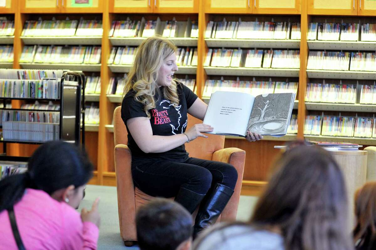 Stephanie Harter Gilmore, who plays Madame de la Grande Bouche, also known as the Wardrobe, in the production of Beauty & the Beast, reads a story to children at the main branch of the Ferguson Library on Friday, Oct. 30, 2015. The library hosted Belle's Book Drive, which collected new and slightly used books to support DOMUS.