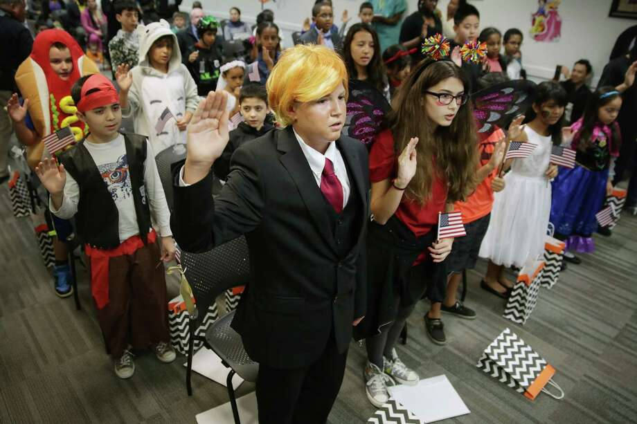 FAIRFAX, VA - OCTOBER 30:  Dressed as Republican presidential candidate Donald Trump, 13-year-old Razvan Godja (C) and 26 other children wear Halloween costumes as they take the Oath of Allegiance during their naturalization ceremony at the U.S. Citizen and Immigration Services Washington Field Office October 30, 2015 in Washington, DC. Godja, who was born in Romania, and the other children became some of the United States' youngest and newest citizens on the day before heading out for the American tradition of trick-or-treating.  (Photo by Chip Somodevilla/Getty Images) Photo: Chip Somodevilla, Staff / Getty Images / 2015 Getty Images
