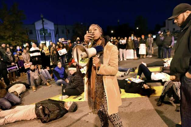 "Amani Olugbala of Capital Area Against Mass Incarceration, center, recites a poem as protestors lay down and block traffic on Henry Johnson Blvd., in front of the Albany Police Department headquarters, on Friday, Oct. 30, 2015, in Albany, N.Y. Social justice advocates and the community protested a grand jury's decision not to charge police who confronted and struggled with Donald ""Dontay"" Ivy on the night he died. (Cindy Schultz / Times Union) Photo: Cindy Schultz / 00033991A"