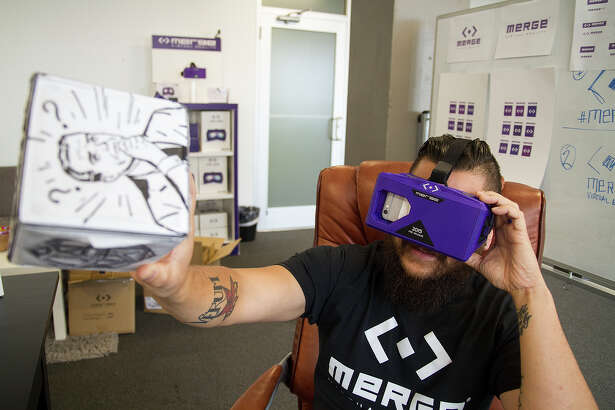 Justin Flores, wearing the Merge VR headset, uses a smartphone's camera for an augmented reality experience at Merge VR's Geekdom office. The headset is one of the first systems of its kind to hit the market.