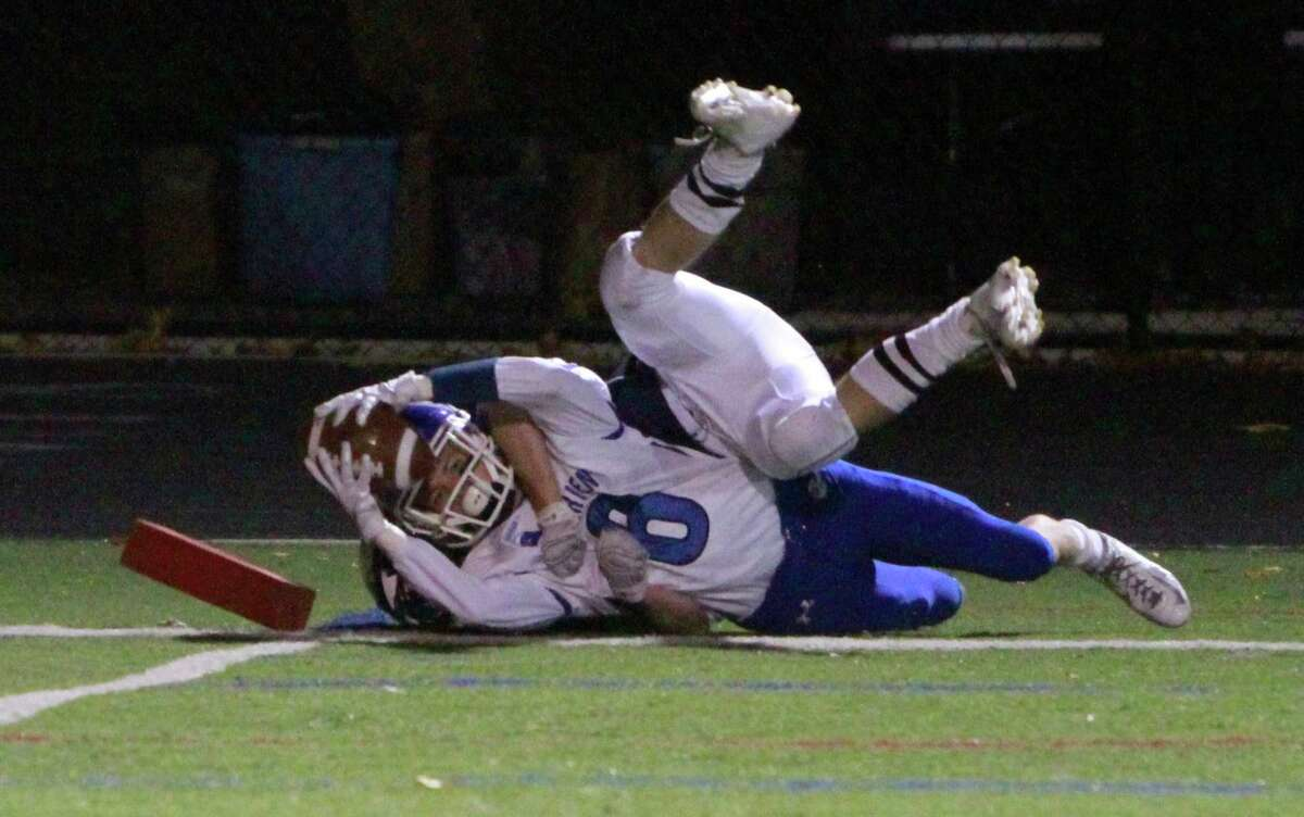 Darien's Colin Minicus stretches in for a touchdown as he is taken down by Wilton's Sam Wright during a varsity football game on Oct. 30, 2015 in Wilton.