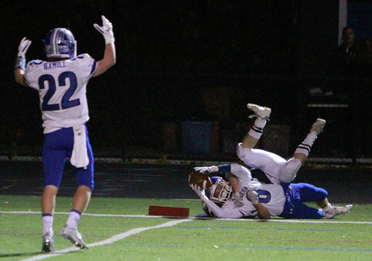 Darien's Hudson Hamill signals touchdown as Colin Minicus stretches in as he is taken down by Wilton's Sam Wright during a varsity football game on Oct. 30, 2015 in Wilton.