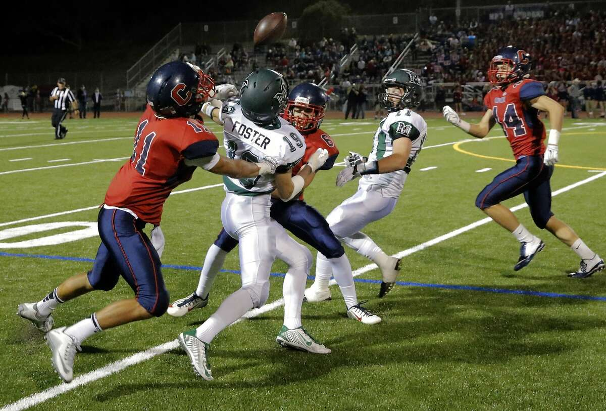 Campolindo's Lev Garcia, 11 and Devin Regan, 6 break up a first quarter pass intended for mIramonte's Nick Foster, 19 as Campolindo Cougars take on the the Miramonte Matadors in Moraga, Calif. on Fri. October 30, 2015.