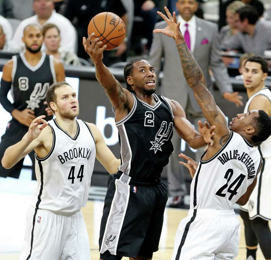 San Antonio Spurs' Kawhi Leonard grabs for control of the ball between Brooklyn Nets' Bojan Bogdanovic (left) and Rondae Hollis-Jefferson during second half action Friday Oct. 30, 2015 at the AT&T Center. The Spurs won 102-75. Photo: Edward A. Ornelas, Staff / San Antonio Express-News / © 2015 San Antonio Express-News