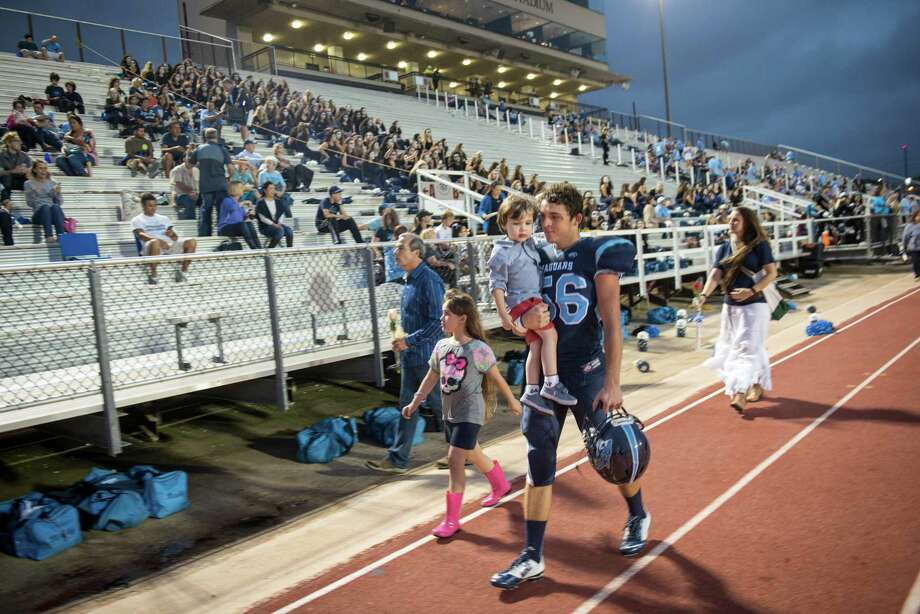Jaguars' Taylor Helton carries his brother Gavin off the field before the start of the District 26-6A high school football game between Johnson and Churchill at Comalander Stadium in San Antonio on Friday, October 30, 2015. Photo: Matthew Busch, Photographer / For The San Antonio Express-News / © Matthew Busch 2015