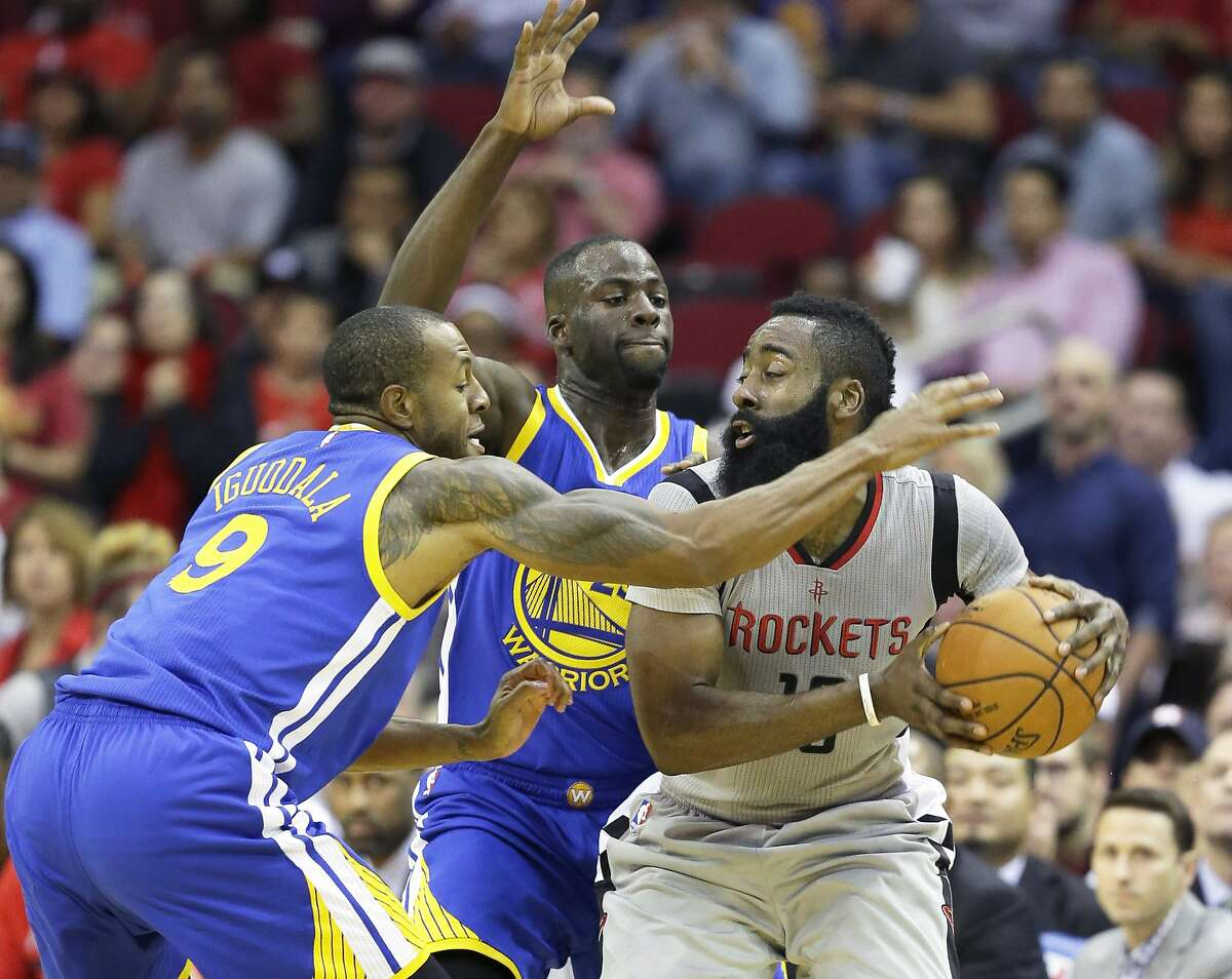 Houston Rockets' James Harden, right, is double-teamed by Golden State Warriors Andre Iguodala, left, and Draymond Green, center, in the first half of a NBA basketball game Friday, Oct. 30, 2015, in Houston. (AP Photo/Pat Sullivan)