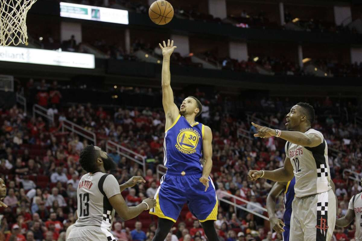 OCT. 30, 2015: WARRIORS 112, ROCKETS 92 WARRIORS 2-0 Golden State Warriors guard Stephen Curry (30) drives to the basket past Houston Rockets guard James Harden (13) and center Dwight Howard (12) during the third quarter of an NBA game at the Toyota Center, Friday, Oct. 30, 2015, in Houston. ( Jon Shapley / Houston Chronicle )