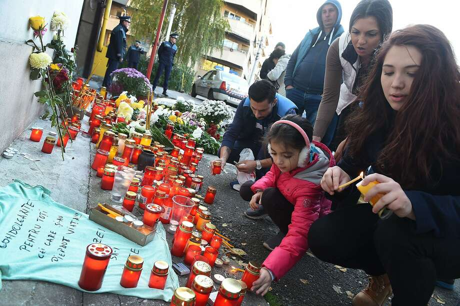 Mourners light candles at a memorial outside the nightclub that burned in Bucharest, Romania. At least 27 people died, and 180 others were injured. Photo: Daniel Mihailescu, AFP / Getty Images