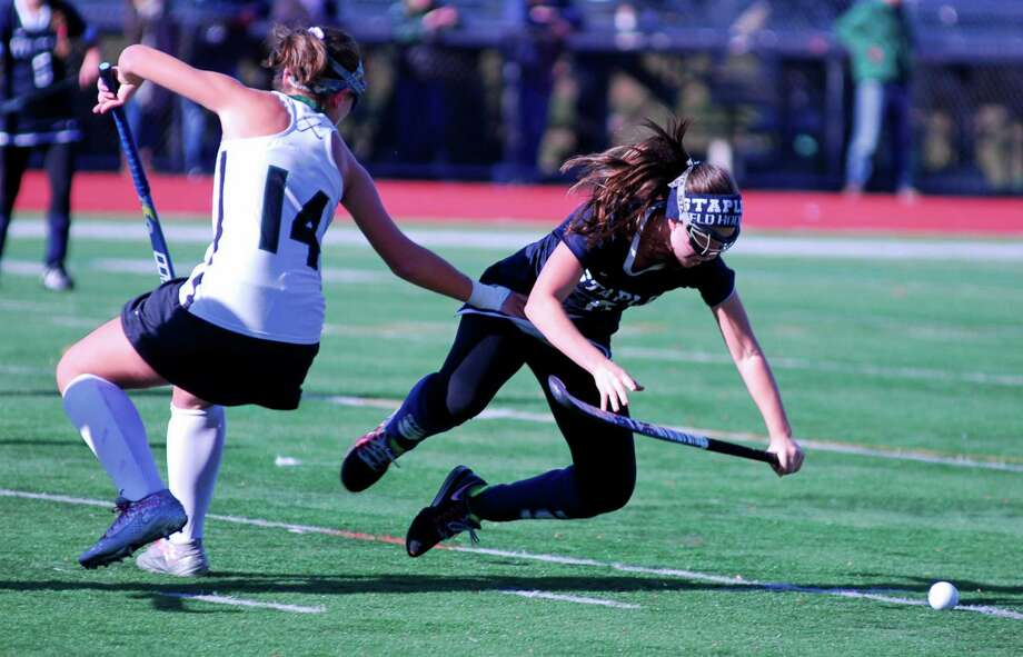 Staples' Skylar Klein, right, is tripped up by a Norwalk player during the FCIAC field hockey quarterfinals on Saturday, October 31st 2015 in Norwalk, Connecticut. Photo: Ryan Lacey/Staff Photo / Westport News Contributed