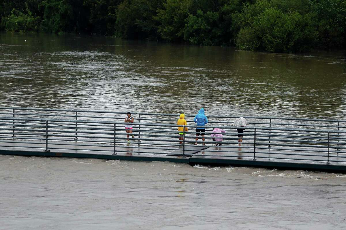 People stand on a pedestrian bridge over White Oak Bayou as heavy rains fall in the area Saturday, Oct. 31, 2015, in Houston.