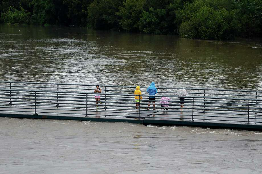 People stand on a pedestrian bridge over White Oak Bayou as heavy rains fall in the area Saturday, Oct. 31, 2015, in Houston. Photo: James Nielsen, Houston Chronicle / © 2015  Houston Chronicle
