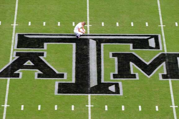 "Texas A&M Yell Leader Steven Lanz prays at midfield above the new Texas A&M ""Blackout"" logo before the start of the South Carolina vs. Texas A&M NCAA college football game on Saturday, Oct. 31, 2015 in College Station, Texas.   (Sam Craft/College Station Eagle via AP) MANDATORY CREDIT"