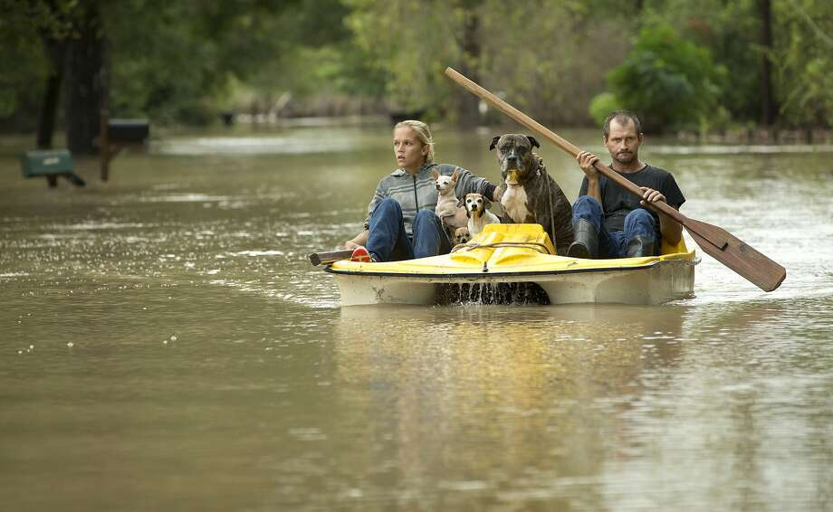Alicia Dougherty and Frank Jackson ferry their dogs out of their flooded home in Garfield, Texas. Dozens of homes on their street, on the banks of the Colorado River, were flooded. Photo: Jay Janner, McClatchy-Tribune News Service