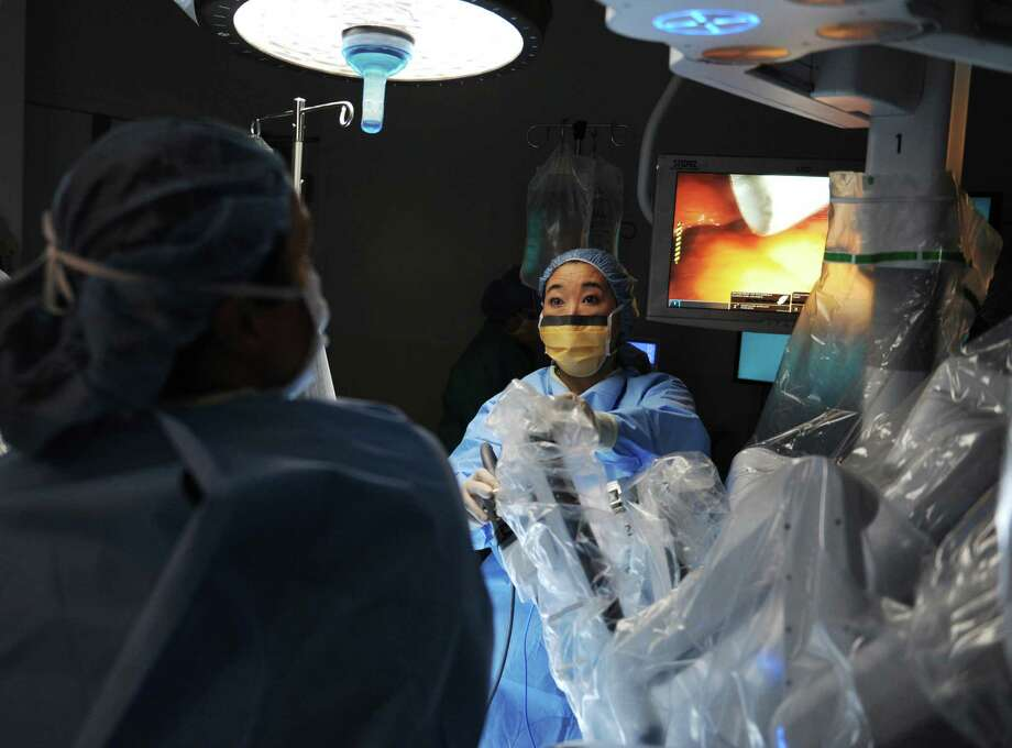 Gynecologic Oncologist Karen Nishida, M.D., sets up the arms on the da Vinci robotic surgery machine before performing a hysterectomy using the machine at Greenwich Hospital in Greenwich, Conn. Thursday, Oct. 29, 2015.  The da Vinci surgical system features a 3D vision system and hand instruments that follow the movement of the surgeon's hands.  The robotic system is minimally invasive, requiring fewer incisions, and enables enhanced vision, precision and control during operations. Photo: Tyler Sizemore / Hearst Connecticut Media / Greenwich Time