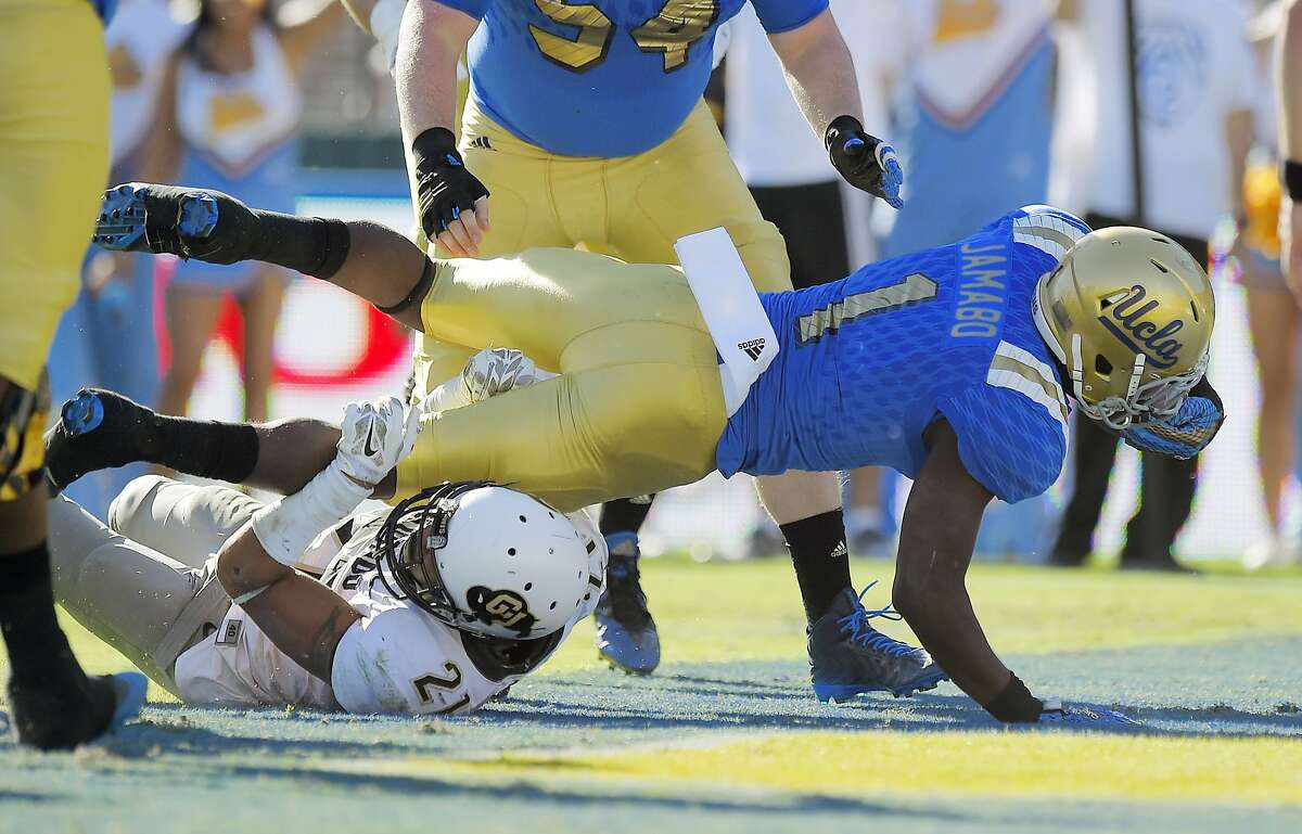 UCLA running back Soso Jamabo, right, dives over Colorado defensive back Jered Bell for a touchdown during the second half of an NCAA college football game, Saturday, Oct. 31, 2015, in Pasadena, Calif. UCLA won 35-31. (AP Photo/Mark J. Terrill)