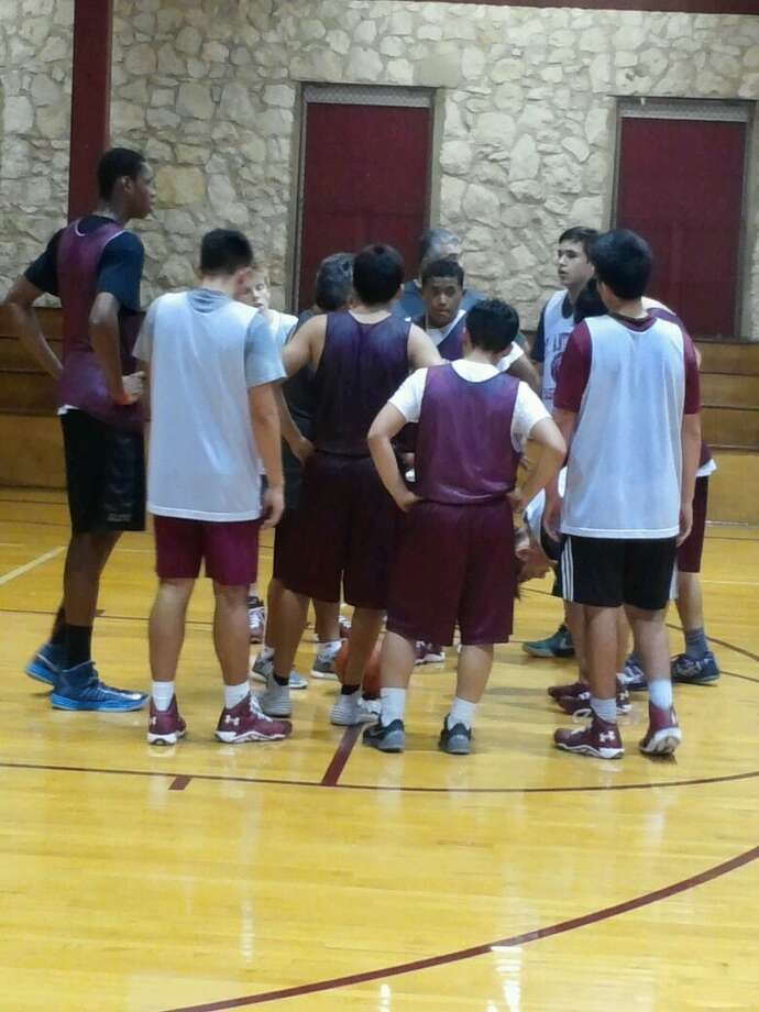 Charles Bassey (left) huddles with his teammates Photo: /