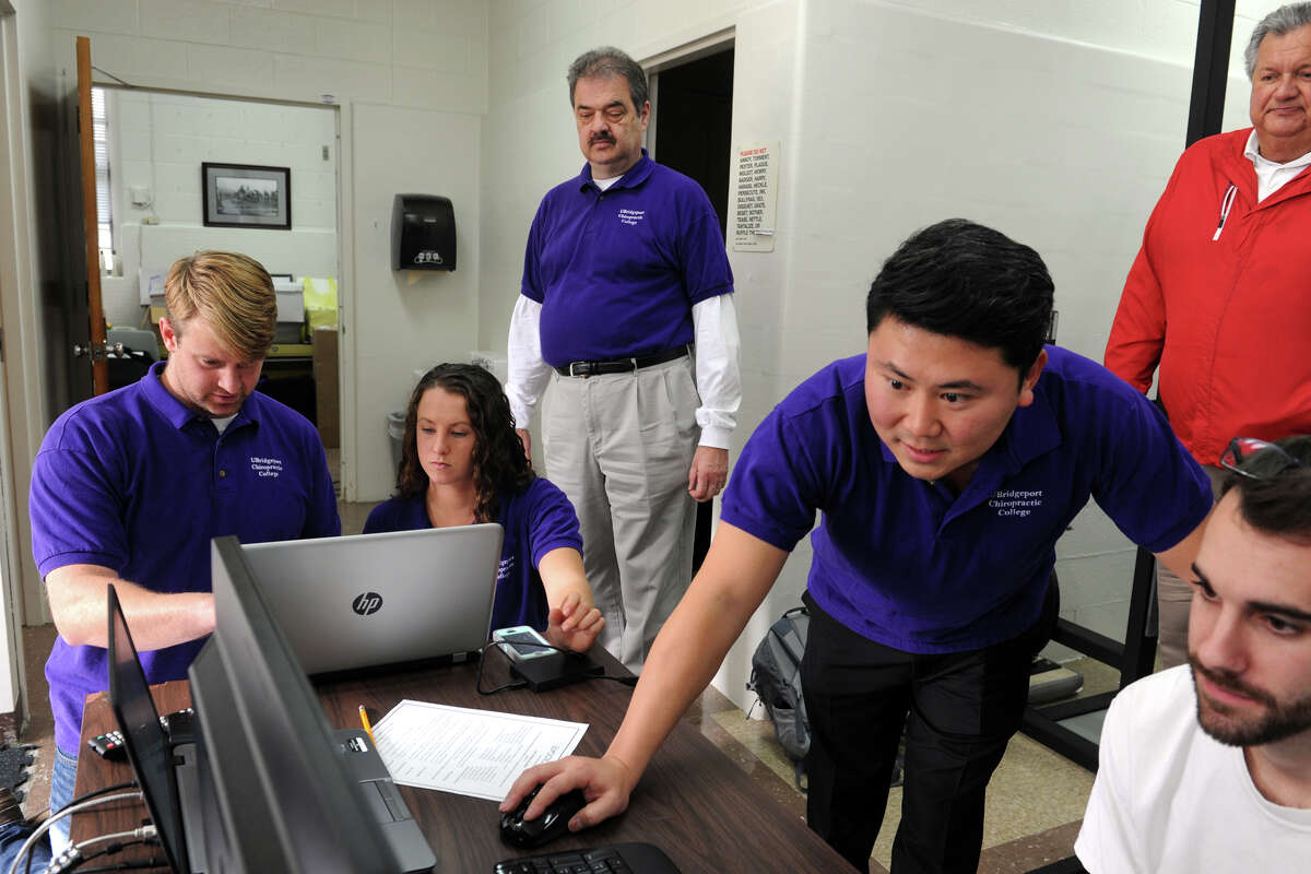 Professor Francis Zolli, standing center rear, looks on as students and staff monitor biomotor skills testing at the University of Bridgeport, in Bridgeport, Conn. Oct. 27, 2015.