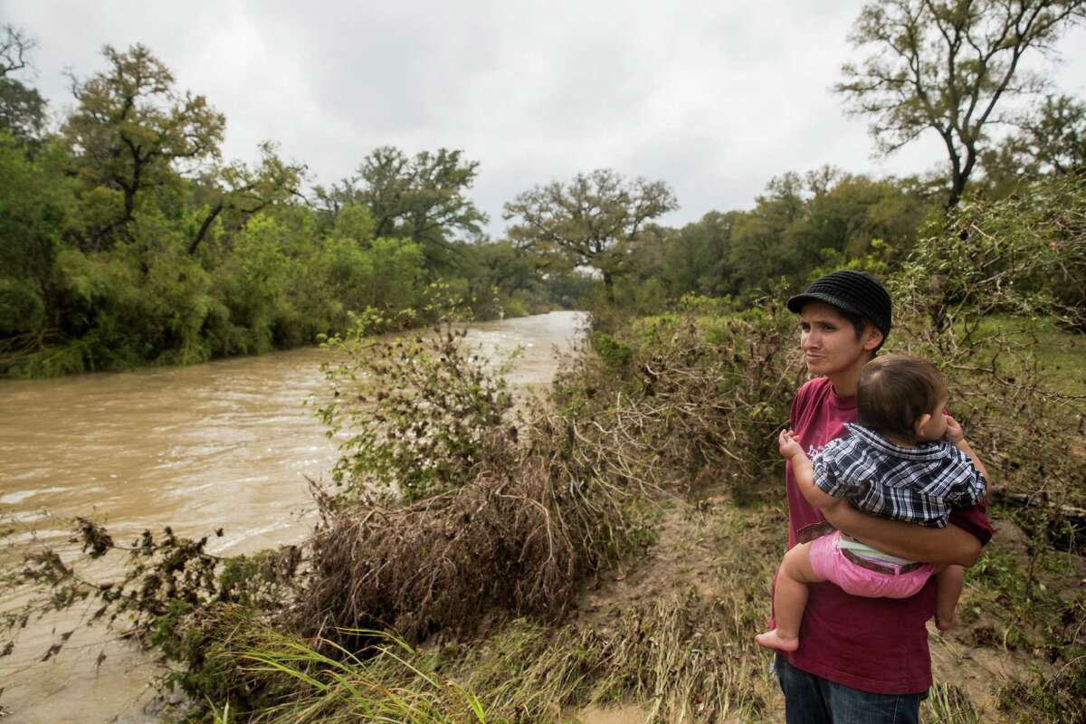 Glenda Bamberger holds Esme Bella Bamberger as she watches the Little Blanco River flow by her family's property in Blanco, Texas on October 30, 2015. Earlier that day, the Bambergers had evacuated because the Little Blanco River was quickly rising again. The flood waters reached the family's previously flood-damaged house, but were approximately four feet lower than they were when the river flooded over Memorial Day weekend of this year.