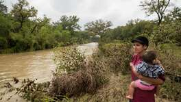 "Glenda Bamberger holds Esme Bella Bamberger as she watches the Little Blanco River flow by her family's property in Blanco, Texas on October 30, 2015.  Earlier that day, the Bambergers had evacuated because the Little Blanco River was quickly rising again.  The flood waters reached the family's previously flood-damaged house, but were approximately four feet lower than they were when the river flooded over Memorial Day weekend of this year. ""You'd think we would be more prepared this time around, but nothing prepares you"" Glenda Bamberger said. ""As much as we try, the girls see us panicking and get worried,"" she said about evacuating."