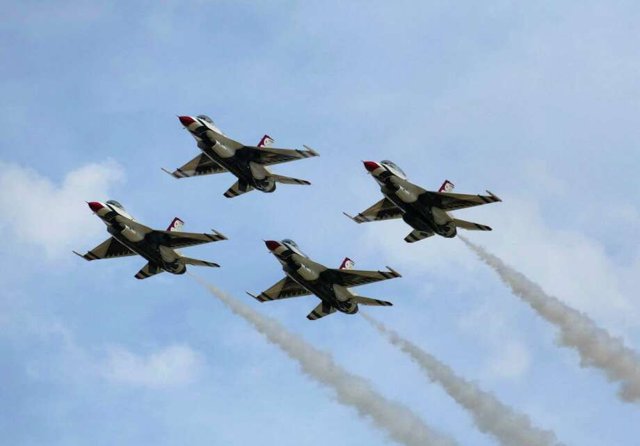 """The Air Force Thunderbirds F-16 aerial demonstration team flies at the 2015 Joint Base San Antonio Air Show at Randolph Air Force Base on Saturday, Oct. 31, 2015. The air show runs through Sunday. Featured performers include the Army's Golden Knights parachute team, the """"Tora Tora Tora"""" Pearl Harbor attack reenactment, T-33 jets and a Tuskegee Airmen P-51 Mustang of World War II vintage. The air show was last held in 2011. Photo: Billy Calzada /San Antonio Express-News / San Antonio Express-News"""