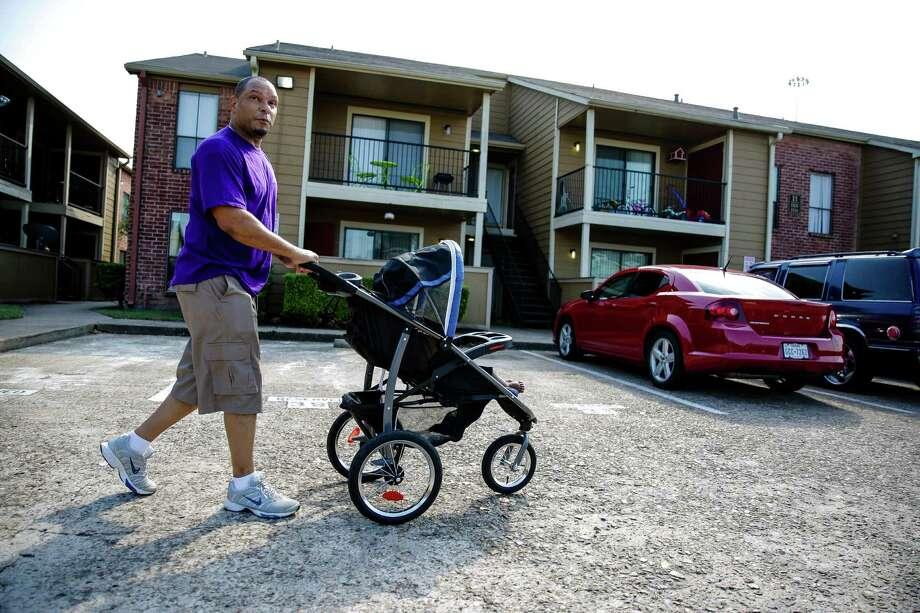 "Darryl Jackson walks around the gated parking lot at the Villa Ana apartments with his seven-month-old son Darryl Jackson Jr. Thursday, Oct. 29, 2015, in Houston. Jackson lives in the voting precinct with the lowest voter turnout in the city. He plans to move away from the area in December with his wife, saying, ""It's a little too dangerous around here. We have to get away from that."" The precinct sits around the intersection of I-59 South and Sam Houston Parkway. Photo: Michael Ciaglo, Houston Chronicle / © 2015 Houston Chronicle"